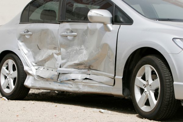 silver car with damage to the passenger side doors after accident