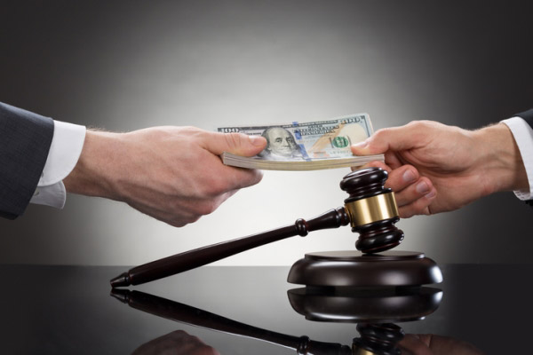hands exchanging money next to a gavel