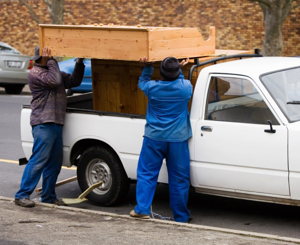 men loading furniture into the back of a pickup truck