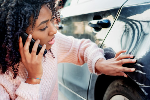 Female driver calling insurance company after a car accident